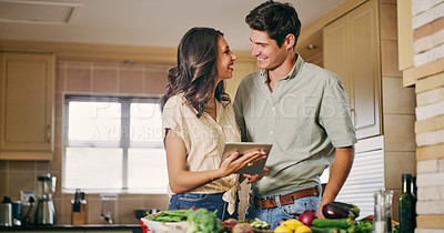 Buy stock photo Shot of a woman showing her boyfriend something on a digital tablet while cooking