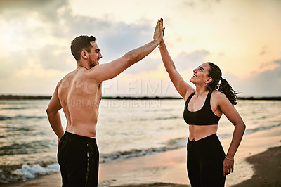 Buy stock photo Shot of two sporty young people giving each other a high five while exercising together outdoors
