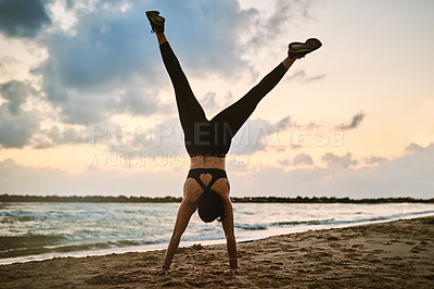 Buy stock photo Shot of a sporty young woman doing a handstand while exercising outdoors