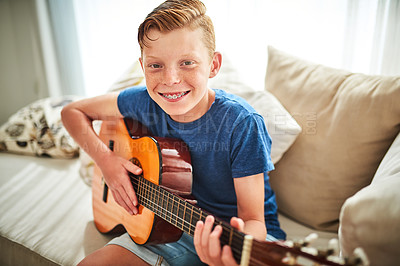 Buy stock photo Portrait of a handsome teenage boy playing the guitar while sitting on a couch at home