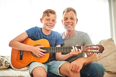 Buy stock photo Portrait of a father teaching his son how to play the guitar at home