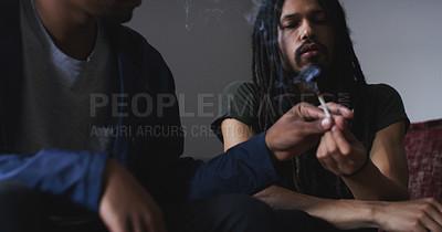Buy stock photo Shot of two young men smoking a marijuana joint at home