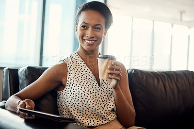 Buy stock photo Shot of a young businesswoman drinking coffee and using a digital tablet while sitting on a couch in her office