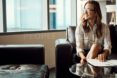 Buy stock photo Shot of an attractive young businesswoman looking out the window while going over some paperwork in her office