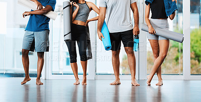 Buy stock photo Shot of a group of unrecognizable people standing and holding their yoga mats inside a studio