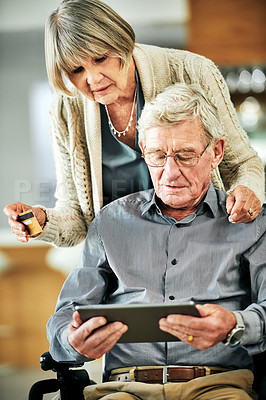 Buy stock photo Shot of a senior man in a wheelchair using a digital tablet and credit card with his wife