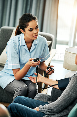 Buy stock photo Shot of a senior woman getting her blood pressure measured during a checkup with a young nurse