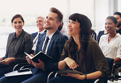 Buy stock photo Cropped shot of a diverse group of businesspeople sitting and laughing while in the office during the day