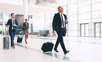 Buy stock photo Full length shot of three businesspeople walking and pulling suitcases while in the office during the day