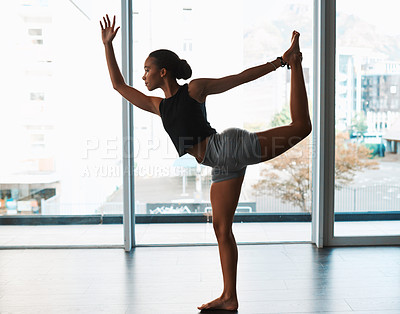 Buy stock photo Full length shot of an attractive young woman standing and stretching while practicing yoga indoors