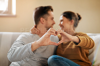 Buy stock photo Shot of a couple forming a heart shape with their hands while sitting together