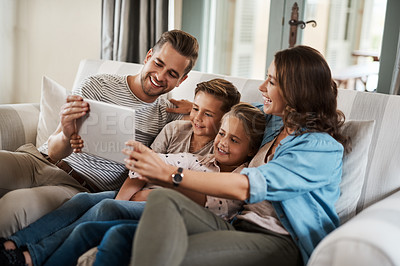 Buy stock photo Shot of a happy young family of four using a digital tablet together on the sofa at home