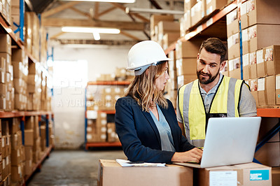 Buy stock photo Shot of a young man and woman using a laptop while working together in a warehouse
