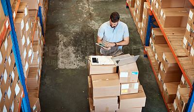 Buy stock photo High angle shot of a handsome young male warehouse worker working on a tablet