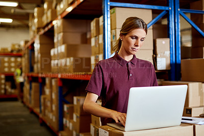 Buy stock photo Shot of a young woman using a laptop in a warehouse