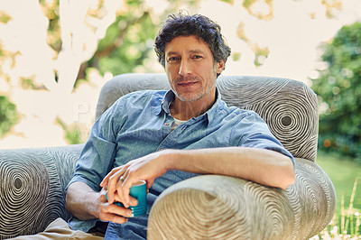 Buy stock photo Shot of a handsome mature man relaxing in a chair and drinking coffee in his backyard