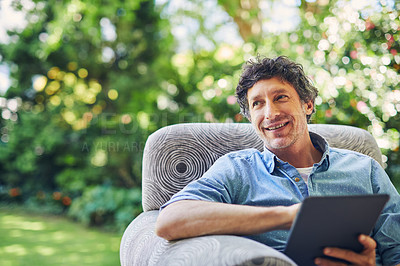 Buy stock photo Shot of a mature man relaxing in a chair and using a digital tablet in his backyard