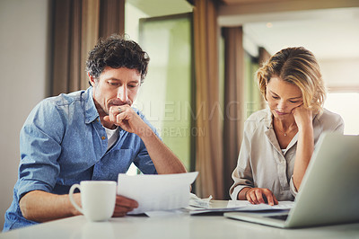 Buy stock photo Shot of a mature couple going over their finances at home