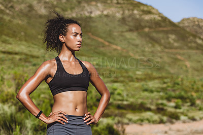 Buy stock photo Shot of a sporty young woman out for a run in nature