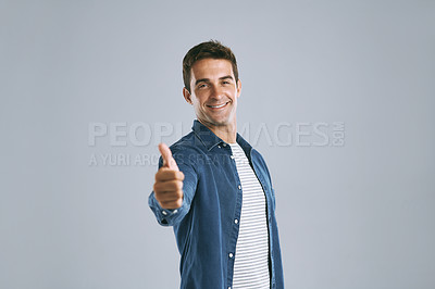 Buy stock photo Cropped shot of a handsome man showing thumbs up against a grey background