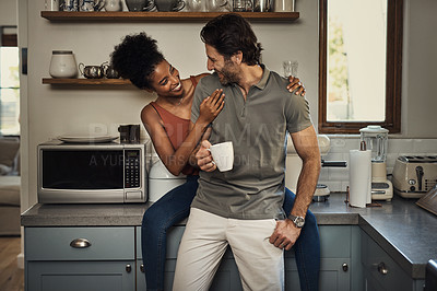 Buy stock photo Cropped shot of an affectionate young couple smiling at each other while spending quality time in their kitchen at home