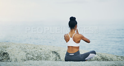 Buy stock photo Rearview shot of an unrecognizable woman sitting cross legged and meditating alone by the ocean during an overcast day