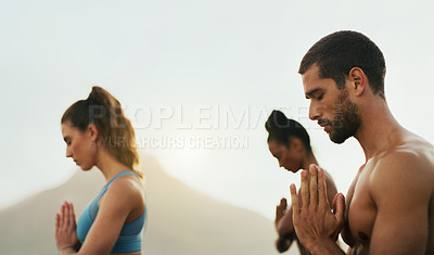 Buy stock photo Cropped shot of a group of young people sitting and meditating together while on the beach during an overcast day