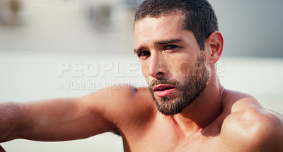 Buy stock photo Cropped portrait of a handsome shirtless young sportsman taking a break after a workout outdoors