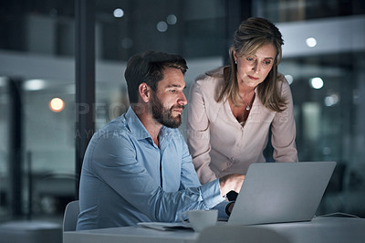 Buy stock photo Shot of two businesspeople working together on a laptop in an office at night