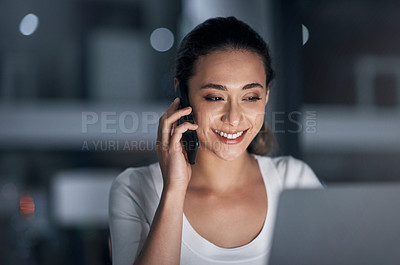 Buy stock photo Shot of a young businesswoman talking on a cellphone while using a laptop in an office at night