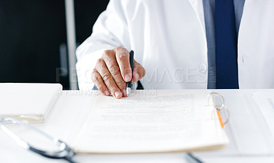 Buy stock photo Closeup shot of an unrecognisable doctor going through paperwork in his office