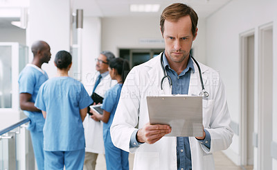 Buy stock photo Shot of a mature doctor using a clipboard in a hospital corridor