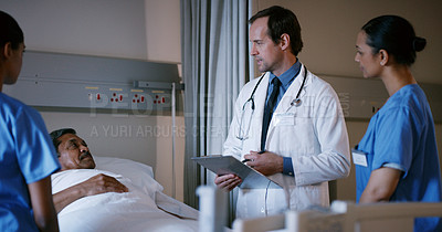 Buy stock photo Shot of a doctor and his colleagues talking to a patient lying in a hospital bed