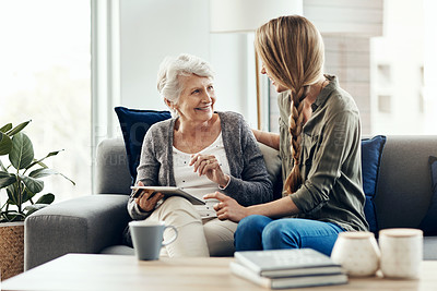 Buy stock photo Shot of a senior woman and her daughter using a digital tablet together
