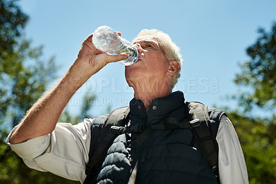 Buy stock photo Shot of a senior man drinking water from a bottle while hiking out in the mountains