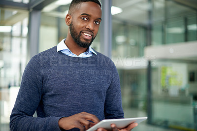 Buy stock photo Portrait of a handsome young businessman using a digital tablet in his office at work