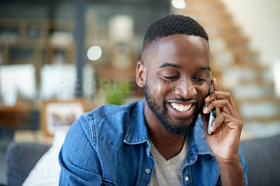Buy stock photo Shot of a handsome young man talking on a cellphone at home