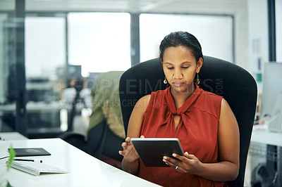 Buy stock photo Cropped shot of an attractive young businesswoman sitting and using a tablet while in the office during the day