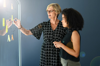 Buy stock photo Cropped shot of two businesswomen brainstorming with notes on a glass wall in a modern office