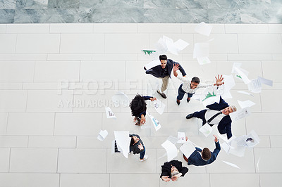 Buy stock photo High angle shot of a group of businesspeople throwing paperwork in the air in celebration