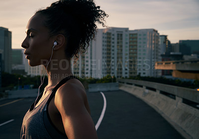 Buy stock photo Cropped shot of an attractive young woman wearing earphones and standing outside in the city after her morning run