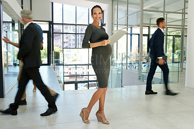 Buy stock photo Full length shot of an attractive young businesswoman standing and holding a tablet while her colleagues walk around her