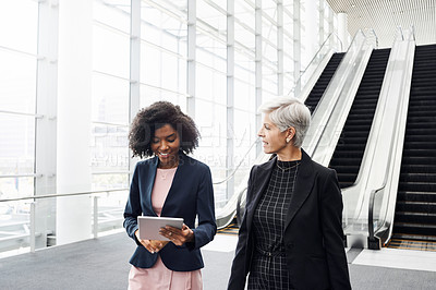 Buy stock photo Cropped shot of two attractive businesswomen using a digital tablet while having a discussion in the workplace
