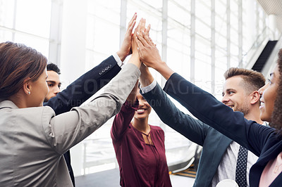 Buy stock photo Cropped shot of a group of young businesspeople joining their hands in solidarity while standing in a modern workplace