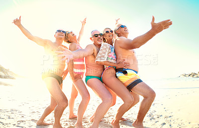 Buy stock photo Cropped shot of a group of senior friends being playful together while out at the beach