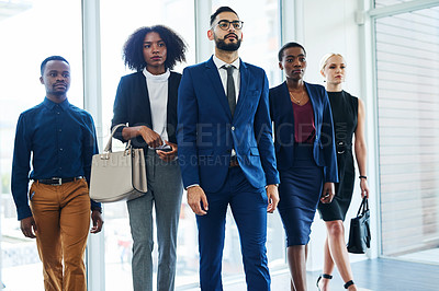 Buy stock photo Cropped shot of a diverse group of businesspeople walking through the offices towards their interview during the day