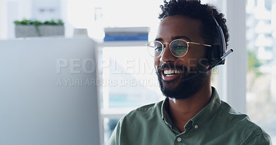 Buy stock photo Shot of a handsome young businessman wearing headsets while working on a computer in his office