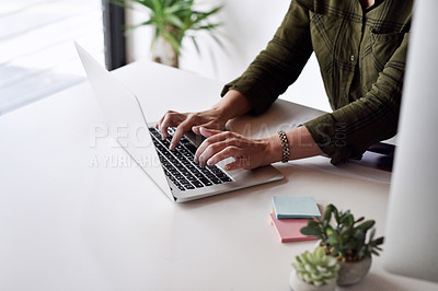 Buy stock photo Cropped shot of an unrecognizable businesswoman typing on her laptop while sitting alone at her desk in the office