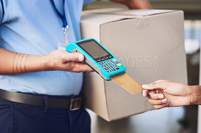 Buy stock photo Closeup shot of an unrecognisable woman using a credit card to pay for her delivery from the courier