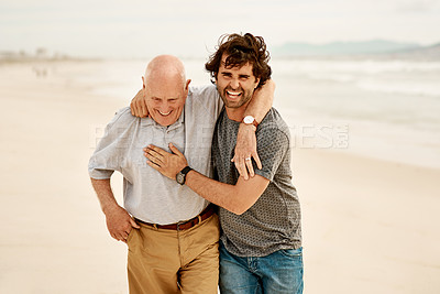Buy stock photo Shot of a senior man and his adult son spending the day together at the beach